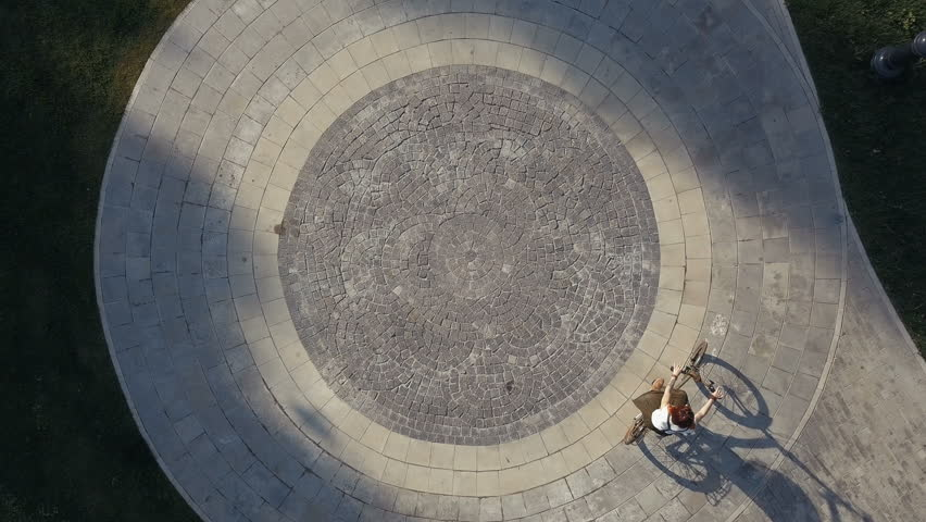 Top view bicycle woman riding a bike on round road in city park. Young woman cycling a bike on circle road at city park in summer park. Woman riding bicycle on paved road in city square drone view | Shutterstock HD Video #31520203