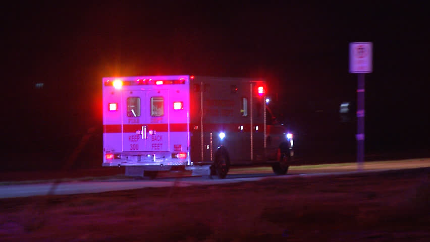 Ambulance drives down long road at night with flashing lights while transporting a patient.