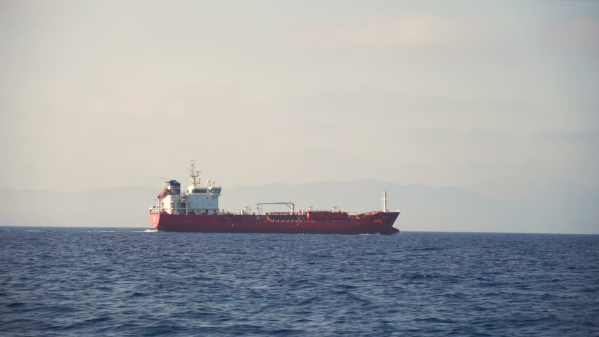 Side view of red cargo ship floating in the sea. Slow motion