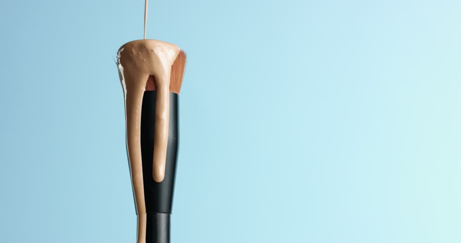 Pouring bb cream or foundation on the bristles of a professional make up brush with black handle isolated on blue #31540216