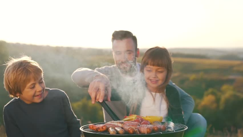 Father with children cook sausages on grill. #31551385
