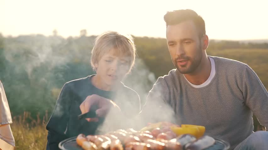 father and son fry sausages on grill.