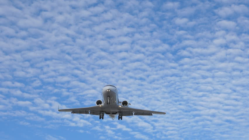 Slow motion shot. Small white private jet flies overhead on final approach and arrival at Pearson International Airport, Toronto, Ontario, Canada. No visible logos.  Royalty-Free Stock Footage #31556146