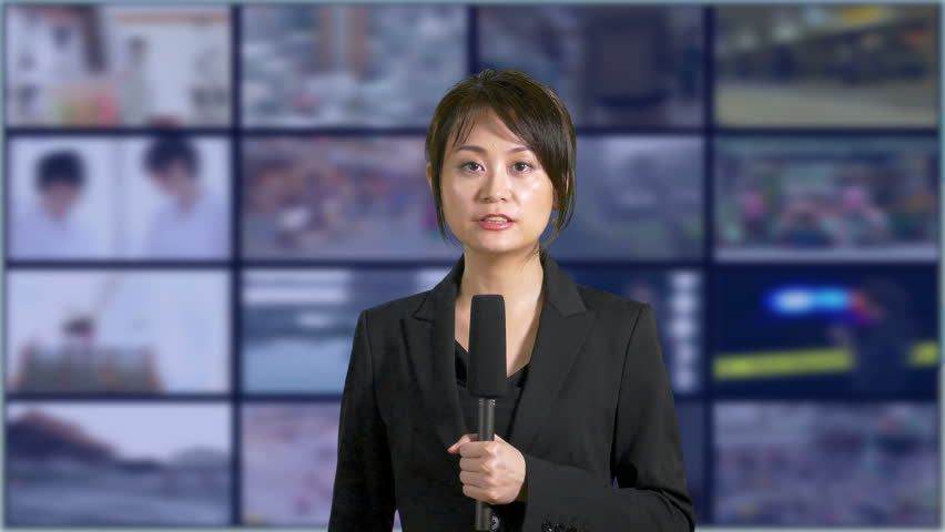 News anchor in TV studio with bank of screens in background