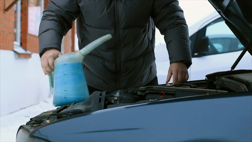 Man fill up a liquid for washing car's glasses