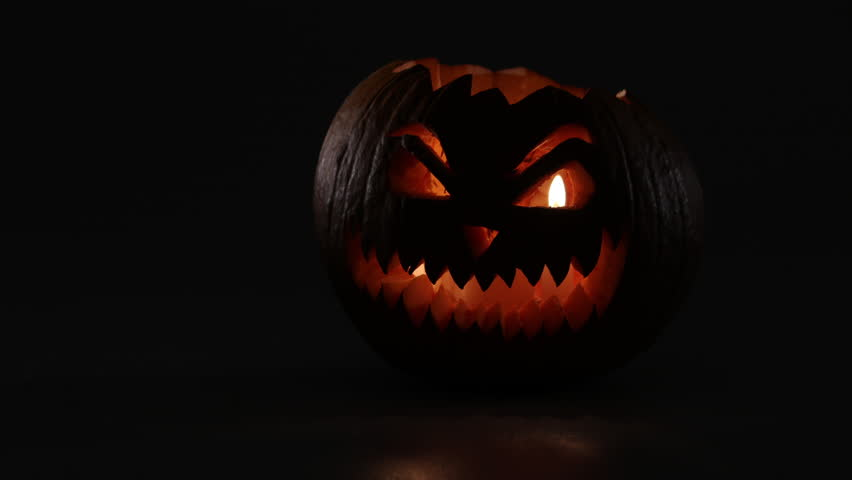 Scary glowing halloween pumpkin comes from dark. | Shutterstock HD Video #31572802