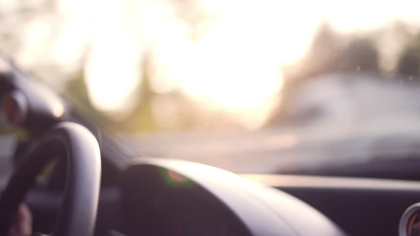 Vintage backlit shot of steering wheel while man driving a car at sunset or sunshine during a holiday, a travel, a business travel or vacation.  | Shutterstock HD Video #31574422