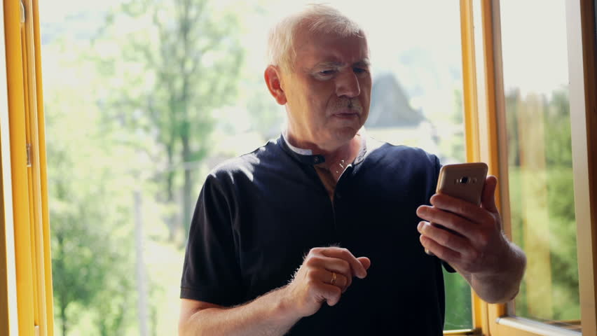 Senior man has problems with his vision while trying to read something on his mobile phone.