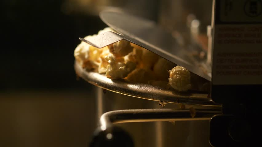 Fresh roasted pop corn pop out of the bowl - pop corn maker in a movie theater
