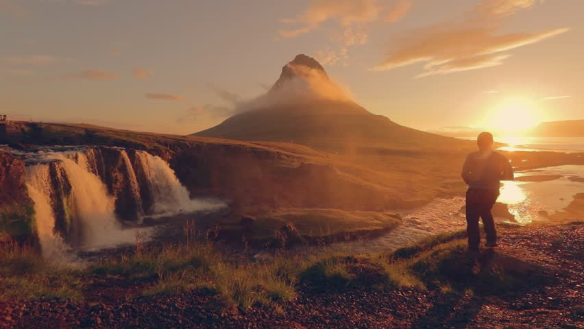 Scene of photographer shoot a green mountain peak and kirkjufellsfoss fall is popular attractions at morning at Iceland, Summertime trip in iceland, shot slow motion