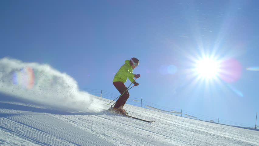 TRACKING SLOW MOTION: Young adult happy skier doing fast turns on a fresh winter morning groomed piste at European ski resort in the Alps during cloudless day. Sun flare shinning in the camera.