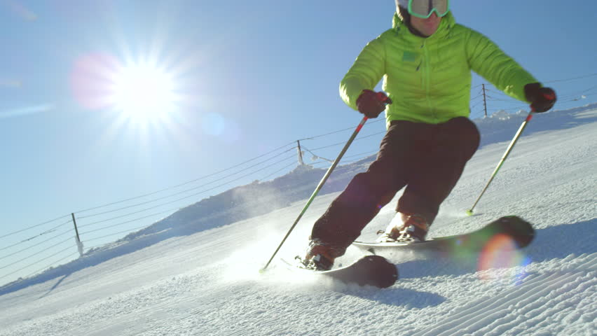 SLOW MOTION CLOSE UP: Young adult recreational skier enjoys idyllic perfect weather in cold winter. Skiing alone on perfectly groomed ski piste at ski resort. Located at the top of the mountain