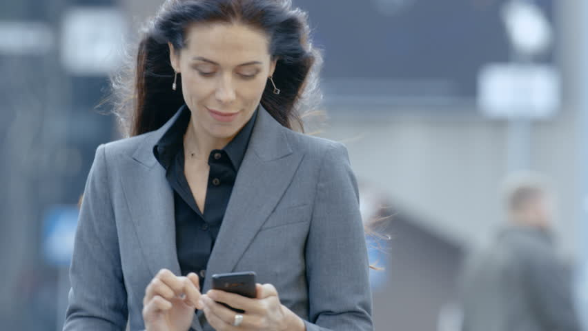 Business Woman in the Tailored Suit Walking on the Busy Big City Street in the Business District, Checks Her Smartphone. Confident Woman on Her Way to do Big Business. Shot on RED EPIC-W 8K Camera.