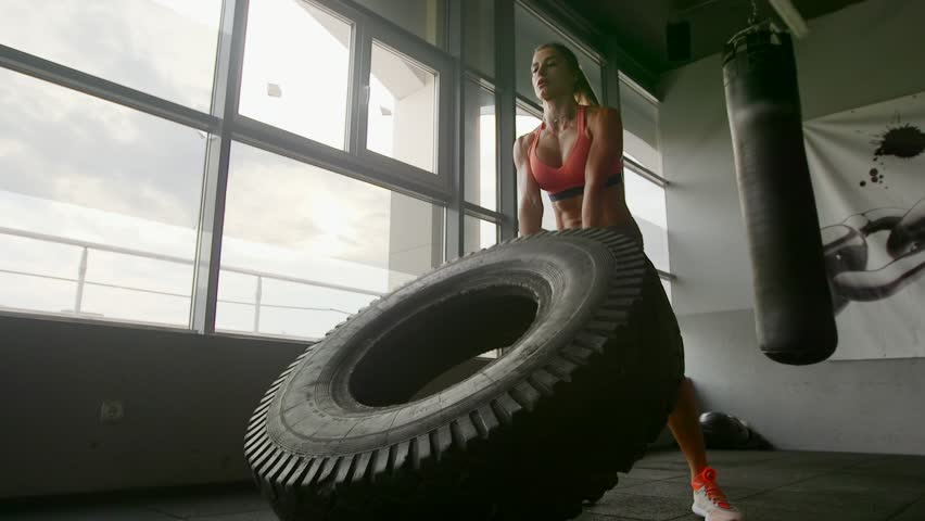 A woman lifts a large tire on an artificial turf field while working out exercising - fitness crossfit exercise workout