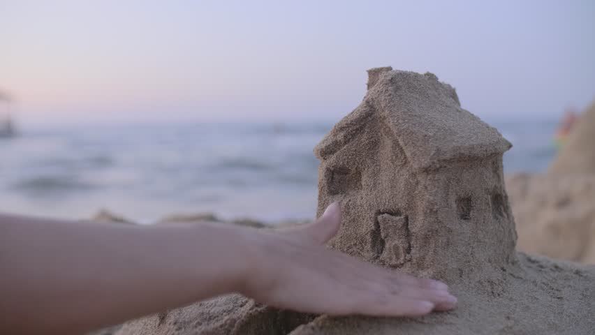Small house with a roof made of sand on the beach at sunset. Property insurance, house protection or saving and security concept. Home under woman's care. Protecting gesture of young girl. #31618651