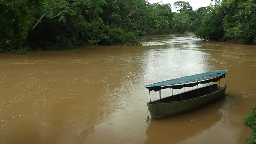 Canoe drifting in the Rio Tiputini in the Ecuadorian Amazon | Shutterstock HD Video #3162742
