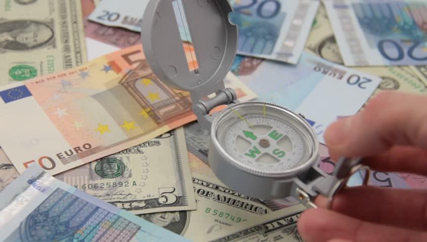Hand puts compass on international paper money. | Shutterstock HD Video #3163501