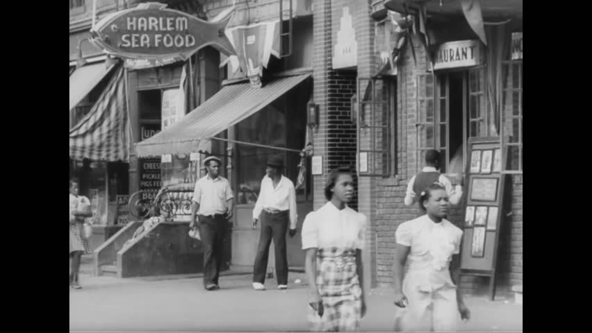 CIRCA 1939 - African Americans walk on a sidewalk in front of a shoe repairing and hat renovating shop as a bus and cars are driven on a stret in Harlem in New York.