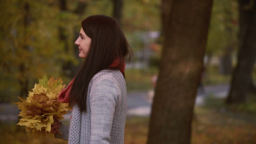 Young girl walks in the park in autumn and holds the leaves in her hands. Footage steadicam shot   Shutterstock HD Video #31683268