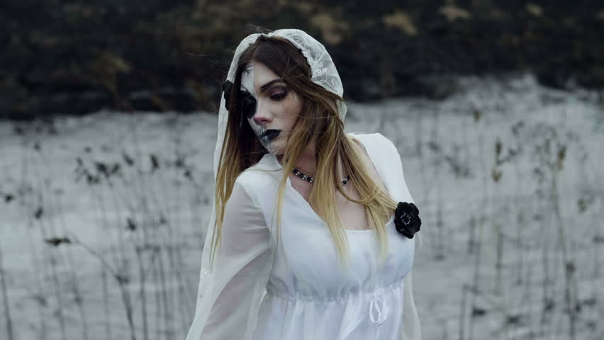 The young beautiful girl with scary makeup for Halloween dressed in a white dress of the bride walking through the field of dried grass. Slow motion. HD   Shutterstock HD Video #31696987