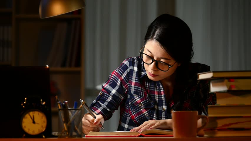 Young woman doing homework at night. Tired hispanic girl and college education. Female student studying for next day exam. mixed race asian chinese model. Royalty-Free Stock Footage #31707367