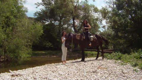 Two women and a horse in a picturesque place.