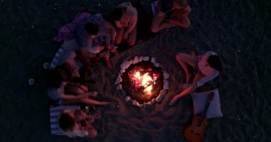 Birds eye view of friends with guitar at beach party roasting marshmallows above bonfire