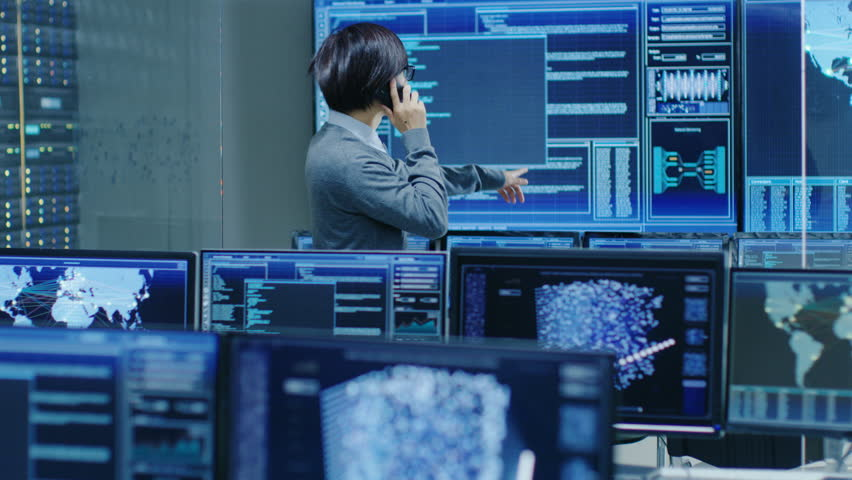 In the System Control Room IT Administrator Talks on the Phone with His Superiors. He's in a High-Tech Facility That Works on the Surveillance, Neural Networks, Data Mining, AI Projects.