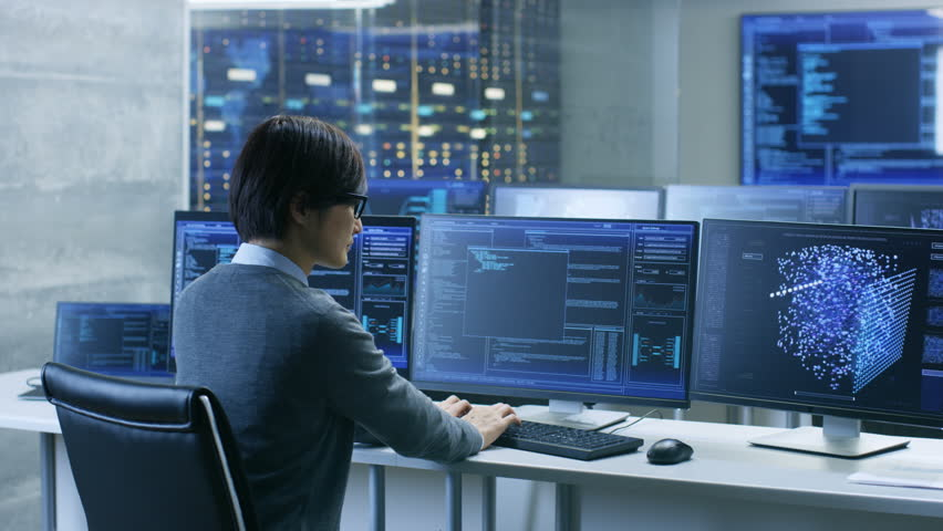 In the System Control Room Technical Operator Works at His Workstation with Multiple Displays Showing Graphics. IT Technician Works on Artificial Intelligence, Big Data Mining, Neural Network Project. | Shutterstock HD Video #31712044