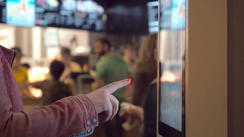 Woman choosing dessert via self-service machine at fast food restaurant. Girl using touch terminal im Mcdonalds makes a quick order through the self-service. Person swipes the screen making an order. | Shutterstock HD Video #31714105