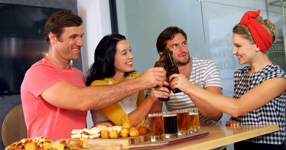 Smiling friends toasting bottle of beer in party at bar 4k #31716310