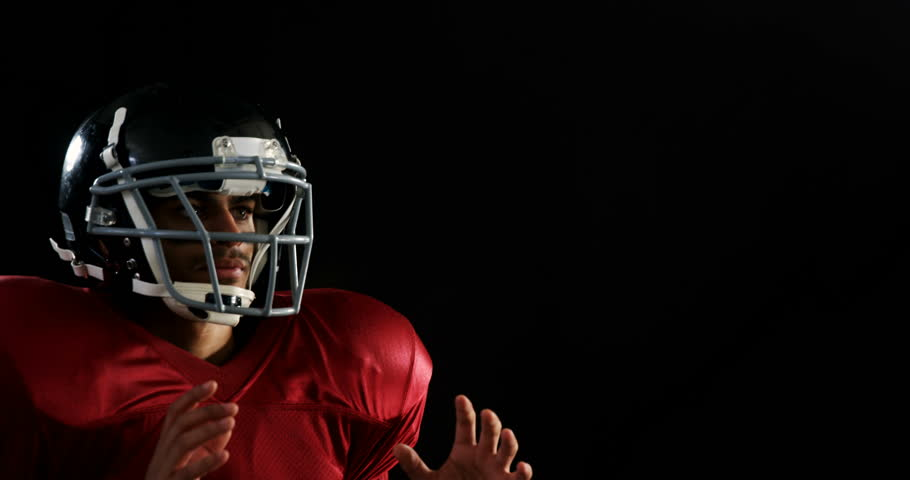 American football player catching the ball against a black background 4k #31718275