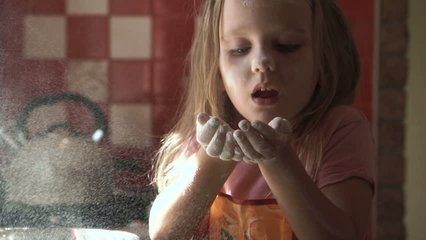 Young girl playing with flour in kitchen while preparing dough