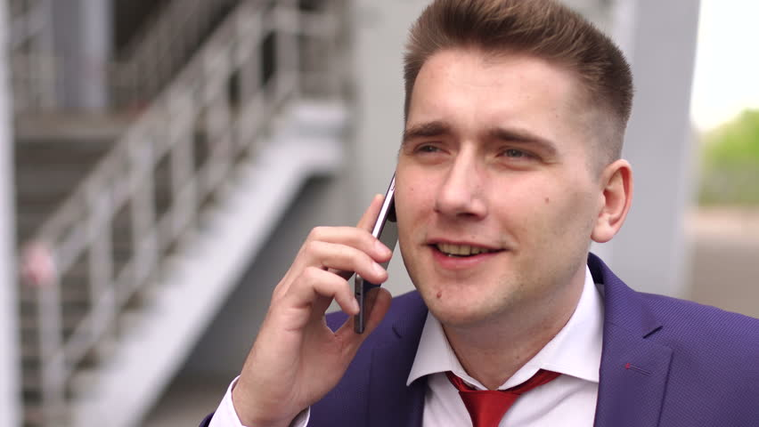 Portrait of a businessman talking on the phone on blurred background outdoor. Close-up. 4K | Shutterstock HD Video #31739266