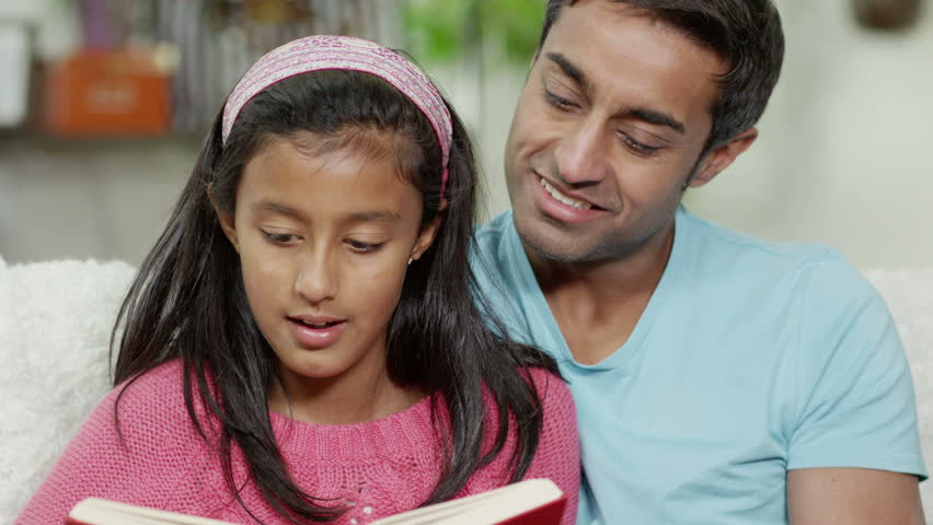 Father and daughter of Indian ethnicity spending time together at home, reading a book