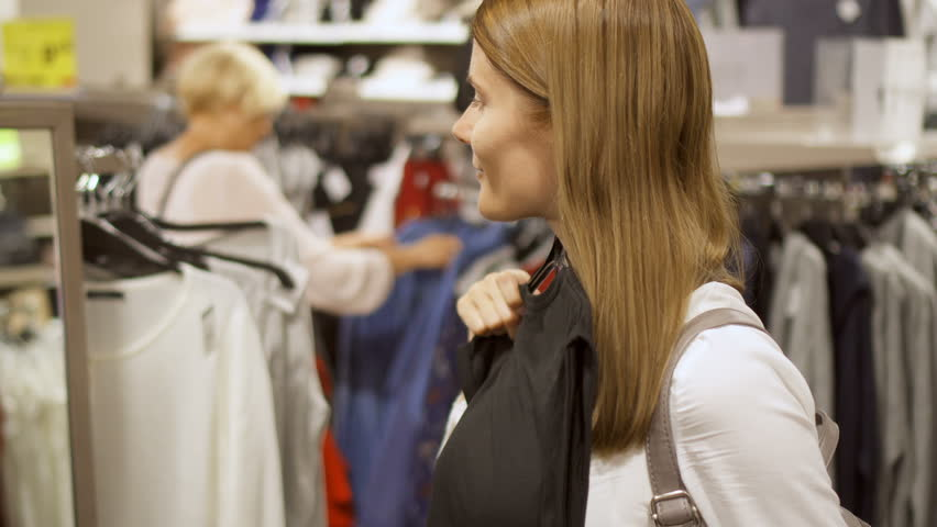 Young woman shopping in mall. Standing near shelves with clothes choosing jacket. Picking up blue coat from rack with clothes. People shopping on background | Shutterstock HD Video #31746682
