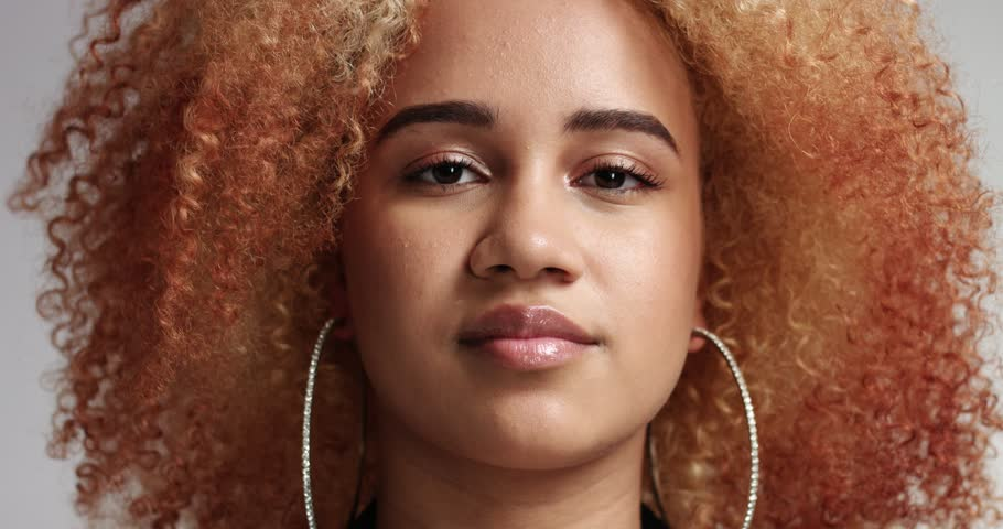 Portrait of a strong confident mixed race black woman with reddish blond afro and large hoop earrings New identity kind of people portrait
