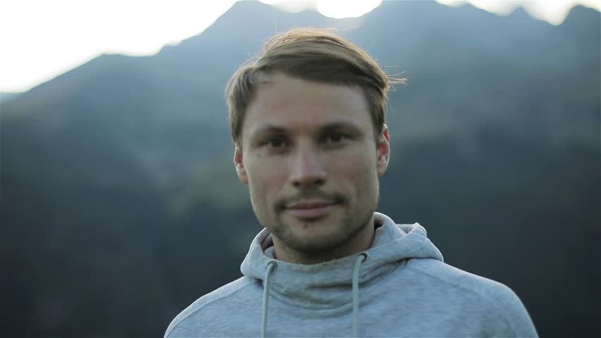 Portrait of man looking at camera face close up outdoors in mountains morning nature. Caucasian handsome confident calm 30s guy with loving kind brown eyes athlete sportsman traveler in grey sweater
