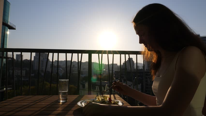 Young woman sit at sunny morning on apartments balcony with fork in salad plate, unhappy with healthy breakfast. Capricious girl look to lettuce leaves and finick with fork | Shutterstock HD Video #31781533