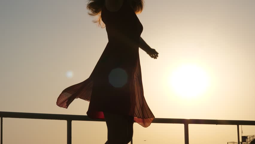 Happy young woman dance in light dress against bright sun, turn around to express positive emotions. Light dress and zephyr skirt fly round, camera tilt up and down. Elegant girl have good moments