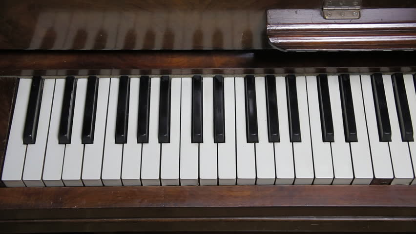 Slow overhead tracking shot of old piano keyboard and reflections in wood
