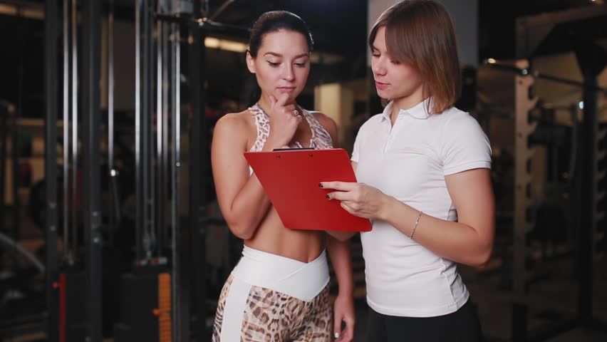 Female personal trainer talking to a woman client in a gym using a tablet for notes. Royalty-Free Stock Footage #31788163