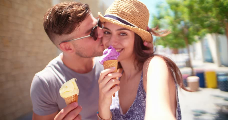 Young hipster couple having fun eating ice cream and taking selfies together on summer holidays