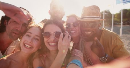 Young multi-ethnic hipster friends on summer island holidays video chatting using smartphone at the beach