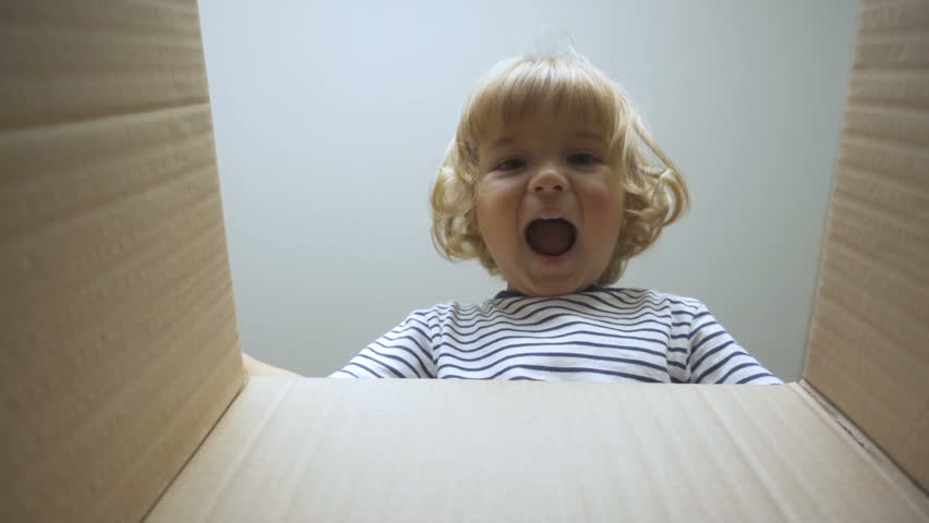 A little boy looks in the box, is surprised and happy to receive a surprise. The child opened a box with a gift. Slow Motion.