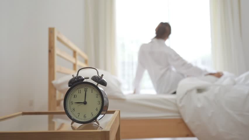 Closeup alarm clock, Young asian woman wake up in the morning and sitting on bed at mirror door side relaxing in holiday with sunlight
