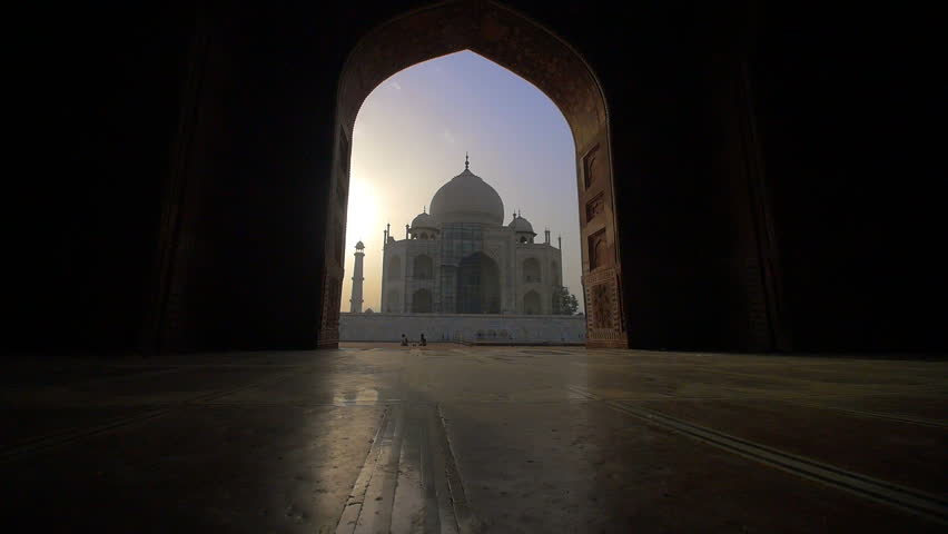 A shot approaching the Taj Mahal through an archway at sunset