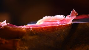 Jamon serrano. Traditional Spanish ham on black close up. Slicing Hamon iberico. Prosciutto close up. 4K UHD video 3840x2160