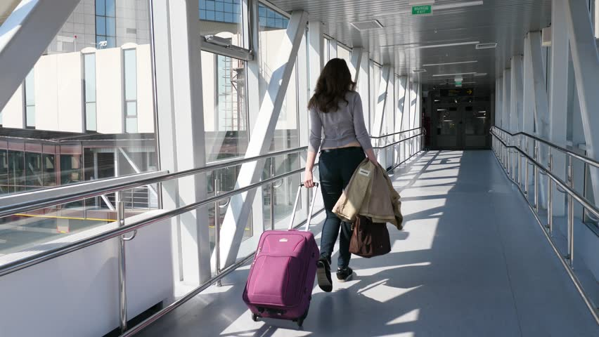 Passenger woman with trolley bag (large cabin luggage) walk through glass walled passage, come to airport terminal from airliner. Bright sun light and dark doorway ahead, follow camera move behind | Shutterstock HD Video #31814767