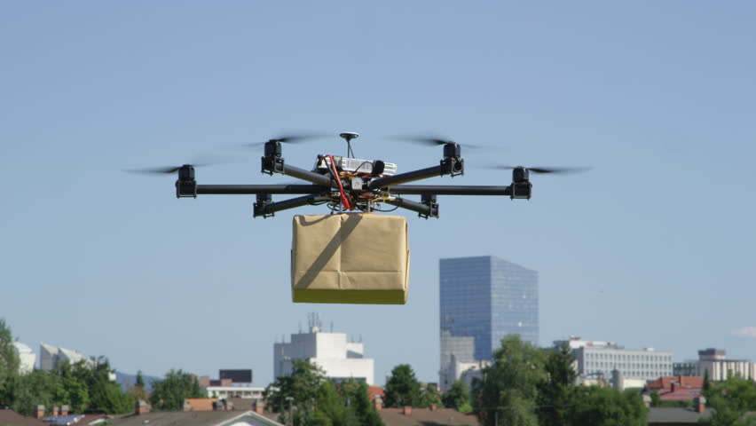CLOSE UP: UAV drone delivery. Multicopter flying big brown package into city. Drone delivering post package to your home. Futuristic shipment by helicopter drone. Multirotor logistics and transport.